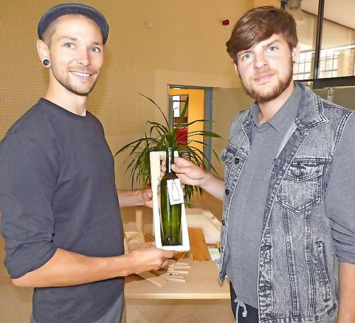 Janek Frölich (l.) und Patrick Giese präsentieren eine Weinflaschenverpackung aus Reststoffen einer Gubener Holzbaufirma. Foto: Jana Pozar/zar1